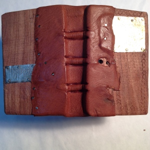"Mesquite wood boards, leather and nickel-silver metal patches. Measures 2.5"" x 4"" fits into back pocket easily."